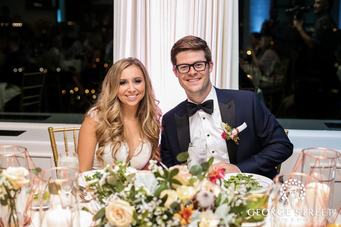 joyous bride and groom at reception table wedding photo