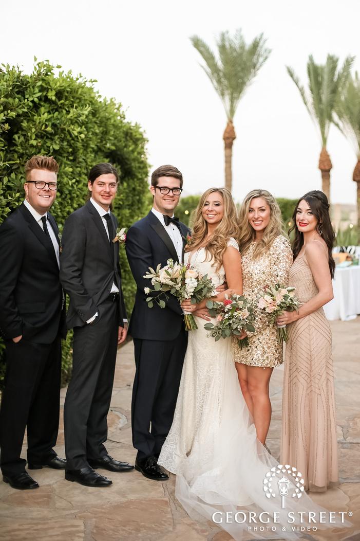 joyous bride and groom with group on walkway wedding photography