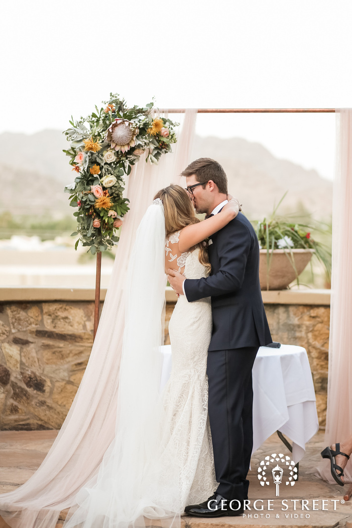 passionate bride and groom first kiss at altar wedding photo