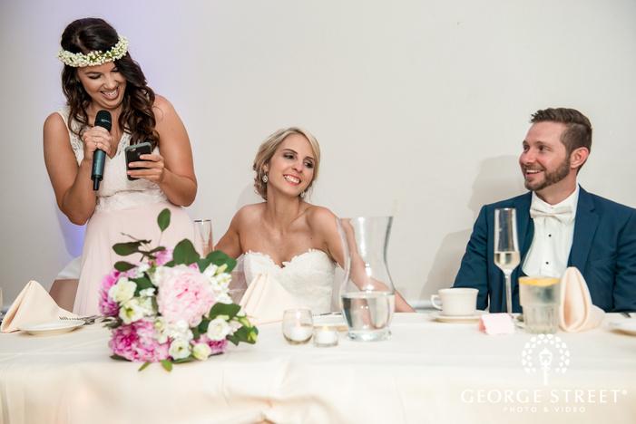 gorgeous couple enjoying wedding speech at reception table wedding photo